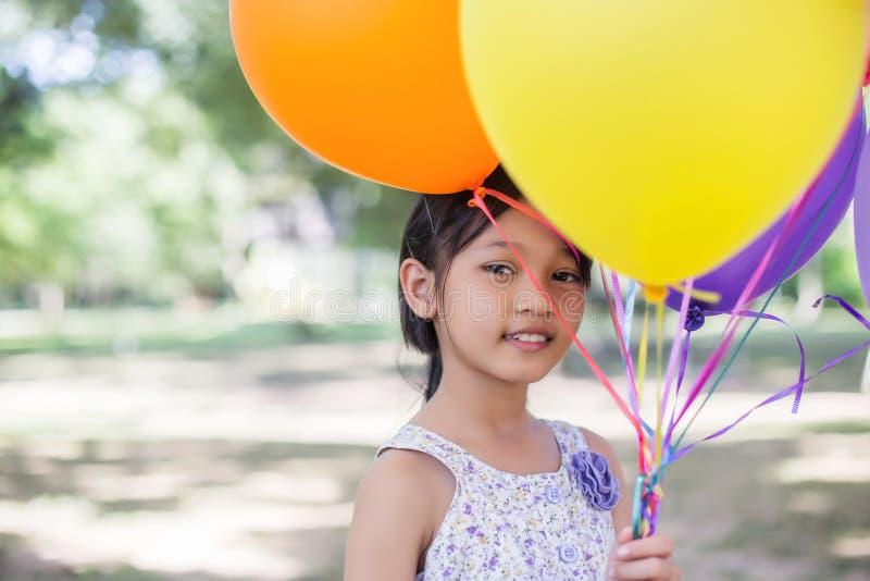 Nettes kleines Mädchen, das bunte Ballone in der Wiese gegen blauen Himmel und Wolken, ausgebreitete Hände hält stockfoto