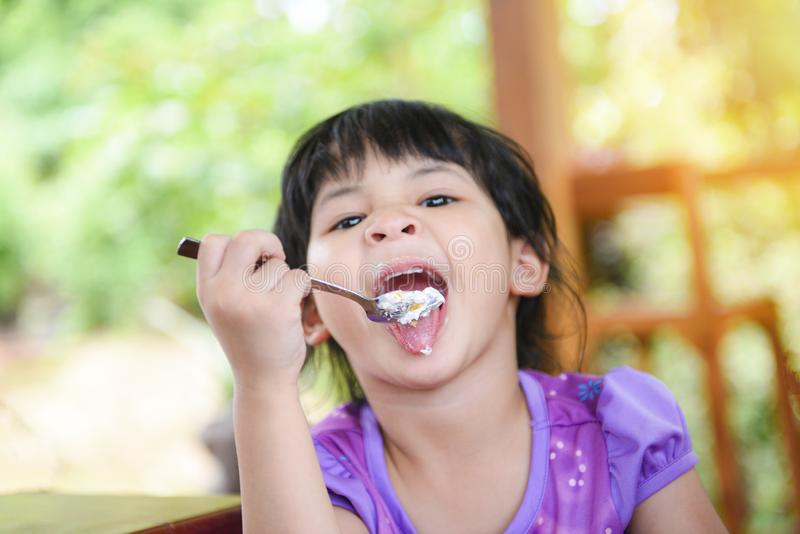 Nettes kleines Mädchen, das den Kuchen/asiatisches Kind glücklich isst und einen Löffel in den Mund mit Kuchen auf Speisetische h lizenzfreie stockfotos