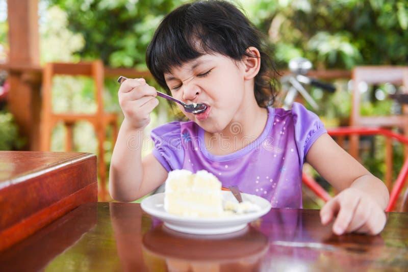 Nettes kleines Mädchen, das den Kuchen/asiatisches Kind glücklich isst und einen Löffel in den Mund mit Kuchen auf Speisetische h lizenzfreie stockfotografie