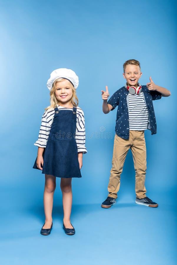 nettes kleines Mädchen, das an der Kamera während Junge mit den Kopfhörern tanzen und zeigen mit den Fingern lächelt stockfotografie