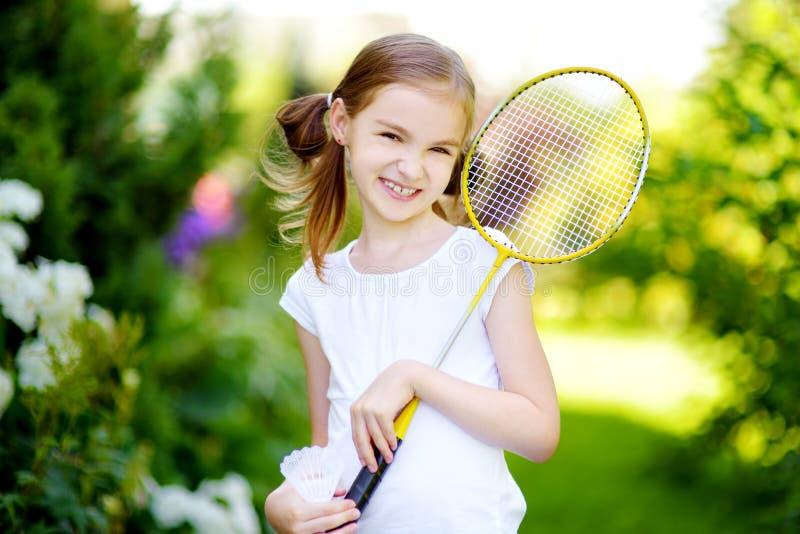 Nettes kleines Mädchen, das draußen Badminton spielt stockbilder