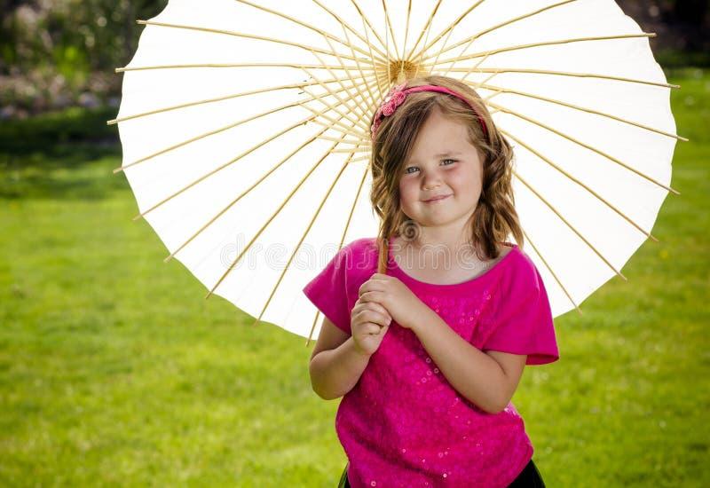 Nettes kleines Mädchen, das draußen einen Sonnenschirm hält stockfotos