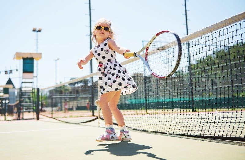 Nettes kleines Mädchen, das draußen Tennis auf dem Tennisplatz spielt stockfotos