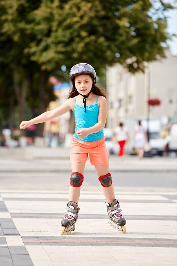 Nettes kleines Mädchen, das draußen zum Rollschuh am schönen Sommertag lernt stockfoto
