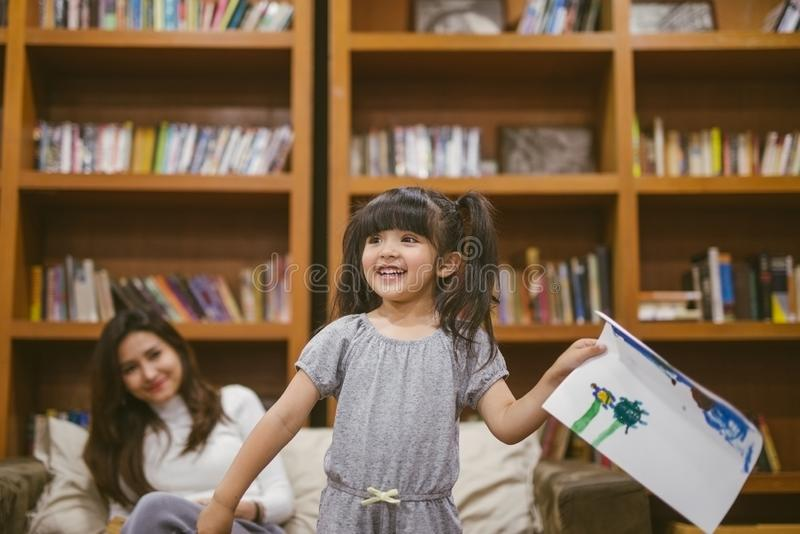 Nettes kleines Mädchen, das ein Bild mit Mutter und ihre Arbeit zu Hause zeigen malt lizenzfreies stockbild