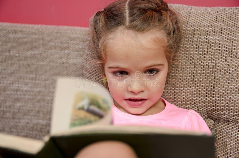 Nettes kleines Mädchen, das ein Buch liest stockfotografie