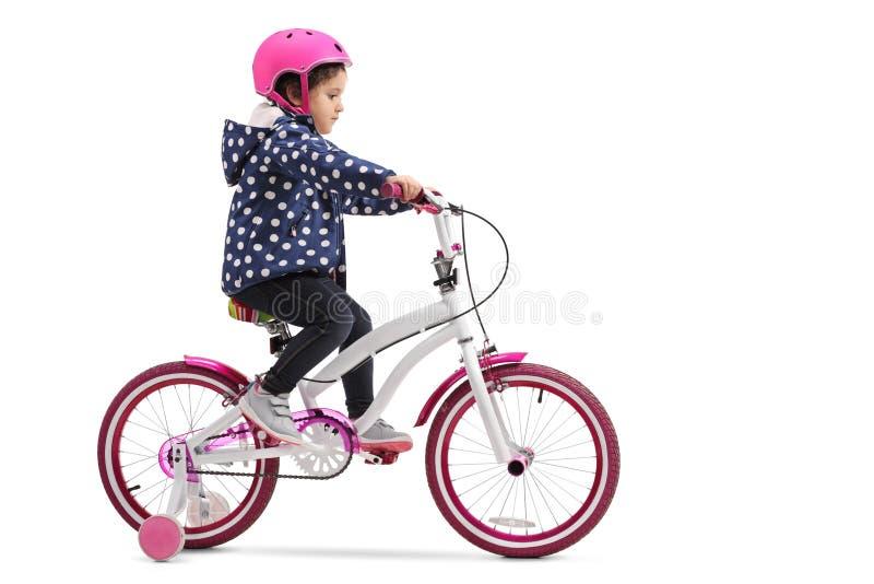 Nettes kleines Mädchen, das ein Fahrrad reitet stockbilder
