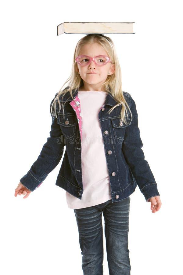 Nettes kleines Mädchen, das eine Bilanz auf ihrem Kopf zieht lizenzfreie stockfotos