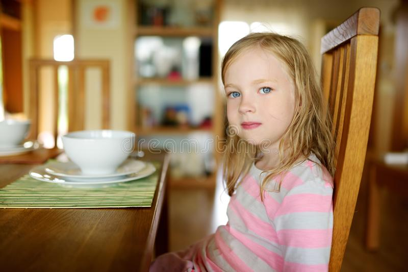 Nettes kleines Mädchen, das eine Suppe im gemütlichen Esszimmer isst Kind, das zu Hause zu Abend isst stockbild