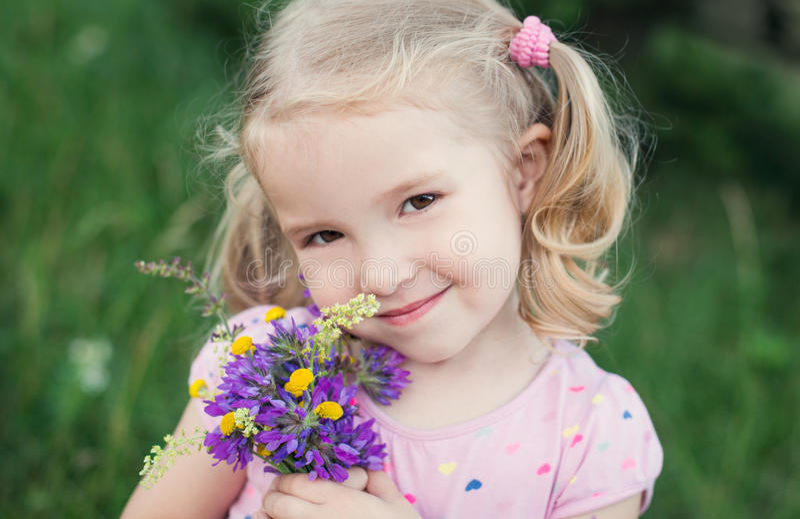 Nettes kleines Mädchen, das einen Blumenstrauß hält lizenzfreies stockfoto