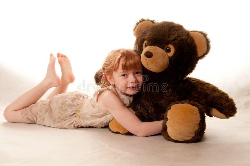 Nettes kleines Mädchen, das einen Teddybären anhält stockfoto