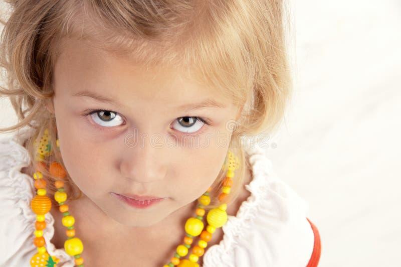 Nettes kleines Mädchen, das für die Kamera aufwirft lizenzfreies stockfoto