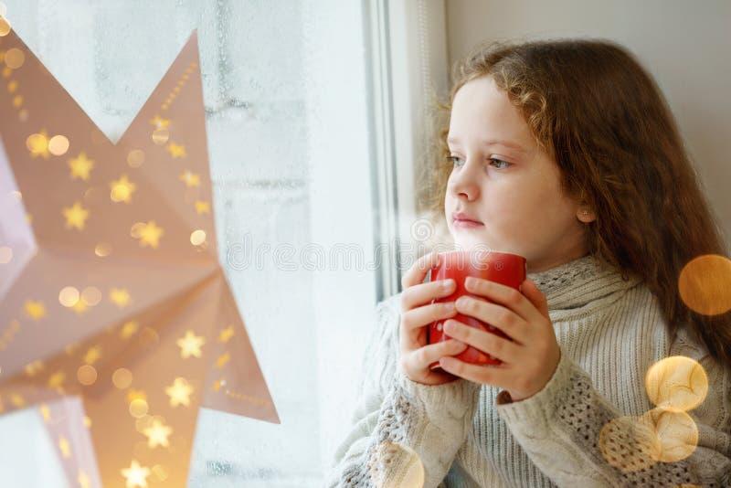 Nettes kleines Mädchen, das am Fenster mit einer Schale heißem Kakao a sitzt lizenzfreie stockfotografie