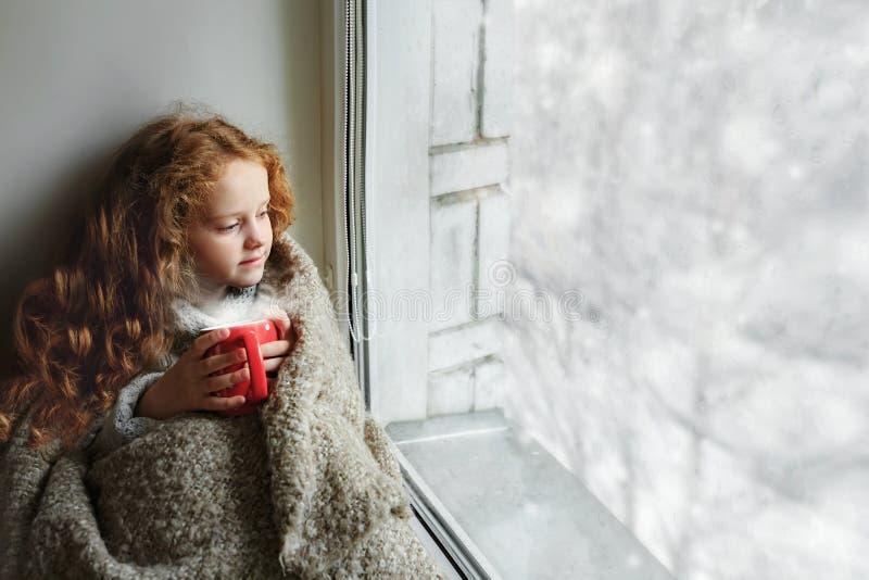 Nettes kleines Mädchen, das am Fenster mit einer Schale heißem Kakao a sitzt stockbild