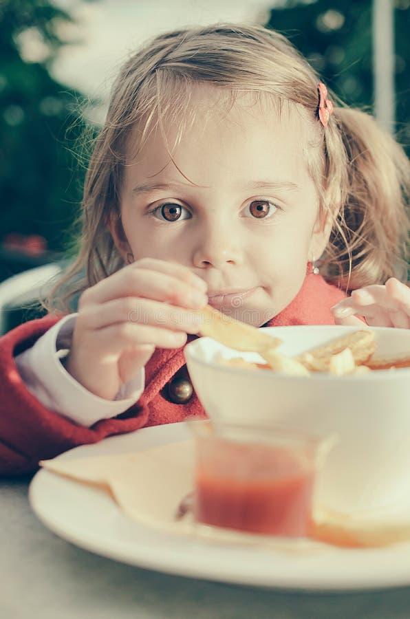 Nettes kleines Mädchen, das Fischrogen und Ketschup isst stockfotos