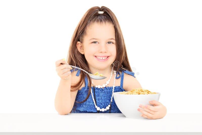 Nettes kleines Mädchen, das Getreide von einer Schüssel isst stockbild