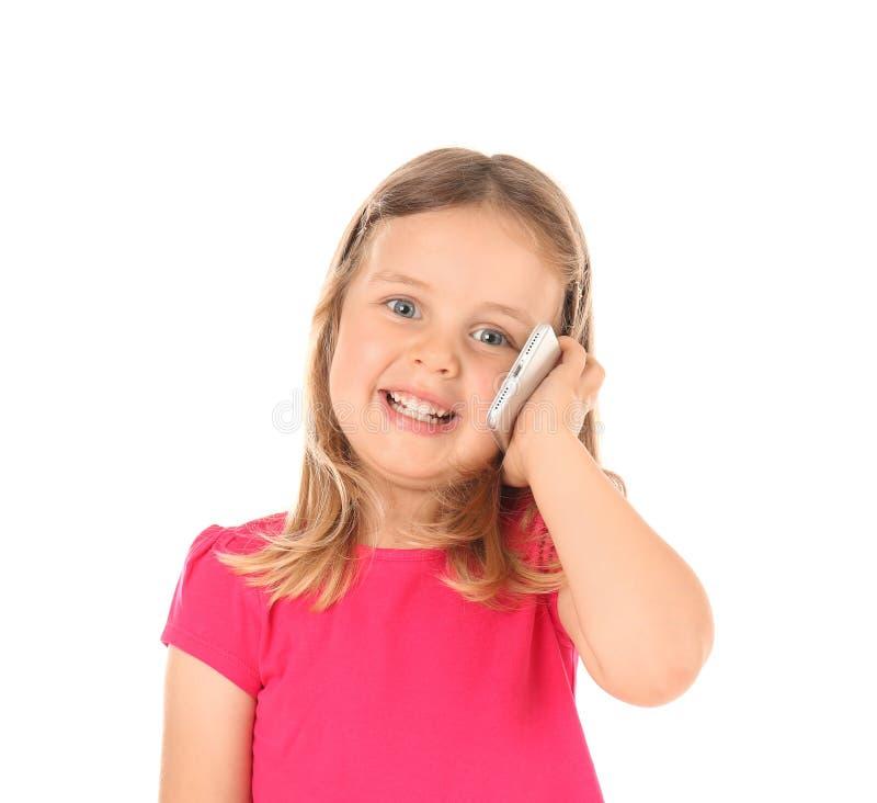 Nettes kleines Mädchen, das am Handy gegen weißen Hintergrund spricht lizenzfreie stockfotografie