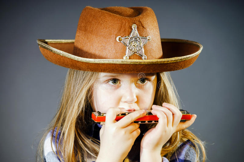 Nettes kleines Mädchen, das Harmonika spielt stockfotos