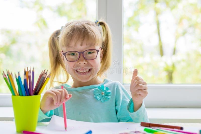 Nettes kleines Mädchen, das Hausarbeit, ein Buch, Färbungsseiten, ein Schreiben und eine Malerei lesend tut Kinderfarbe Kinderabg lizenzfreie stockbilder