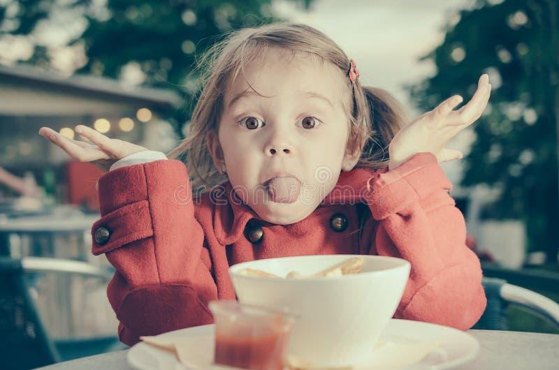 Nettes kleines Mädchen, das heraus ihr toungue beim Essen haftet lizenzfreie stockfotografie