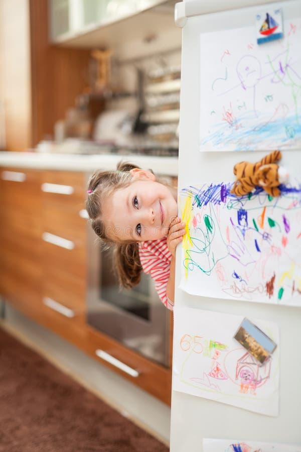 Nettes kleines Mädchen, das hinter Kühlschranktür in der Küche lächelt lizenzfreies stockbild