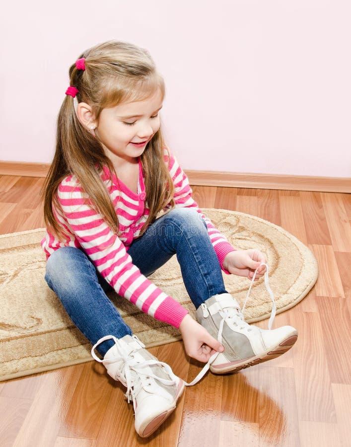 Nettes kleines Mädchen, das ihre Weißschuhe bindet stockfotos