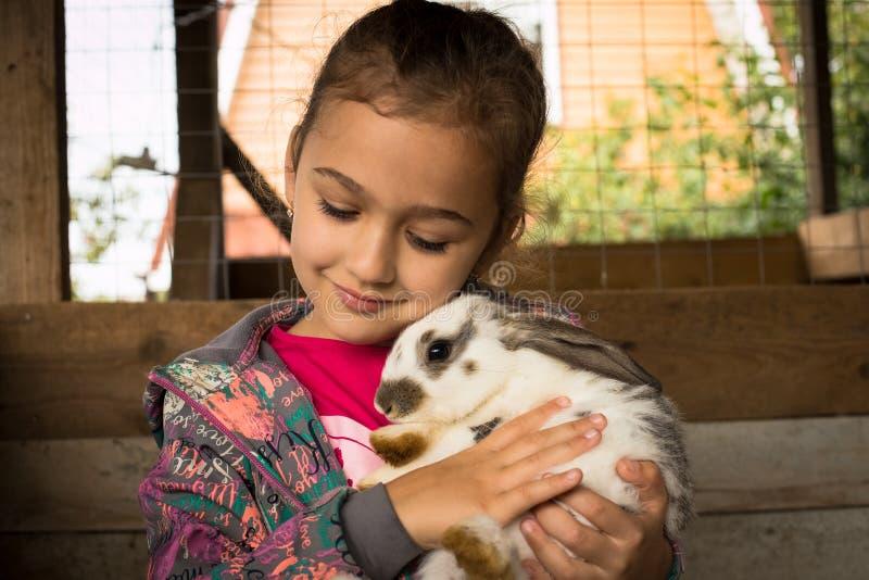 Nettes kleines Mädchen, das in ihrem Umarmungs-netten Kaninchen hält stockfotos