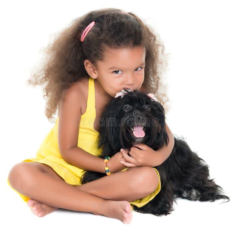 Nettes kleines Mädchen, das ihren Schoßhund küsst stockbilder