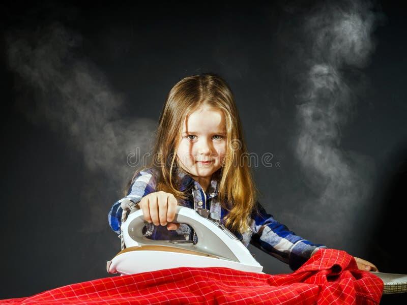 Nettes kleines Mädchen, das Ihrer Mutter durch das Bügeln von Kleidung, Contras hilft stockbild