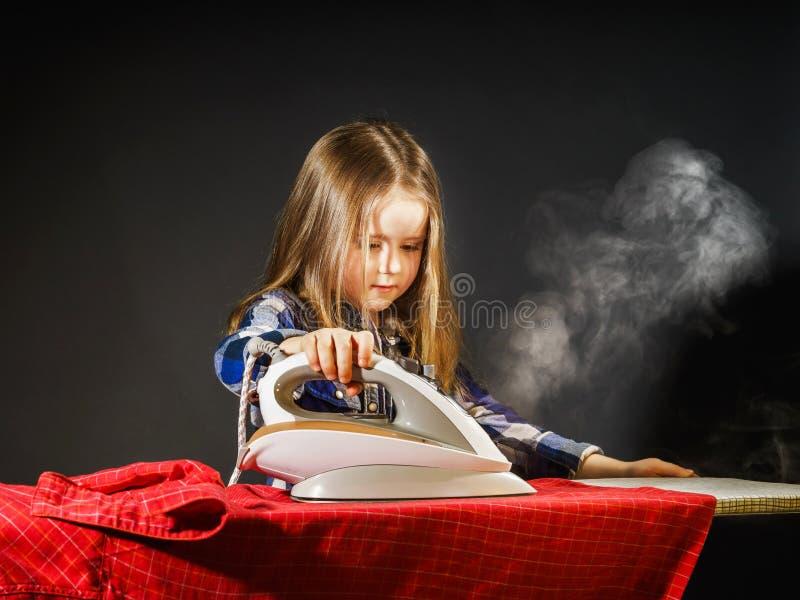 Nettes kleines Mädchen, das Ihrer Mutter durch das Bügeln von Kleidung, Contras hilft lizenzfreie stockbilder