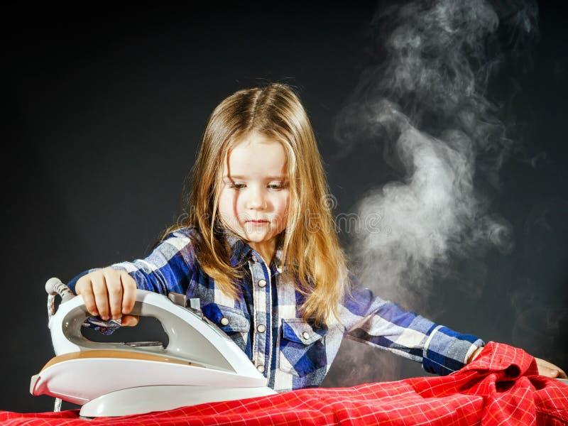Nettes kleines Mädchen, das Ihrer Mutter durch das Bügeln von Kleidung, Contras hilft stockfotografie