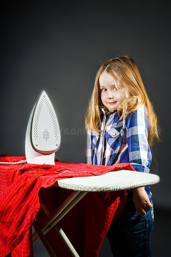 Nettes kleines Mädchen, das Ihrer Mutter durch das Bügeln von Kleidung, Contras hilft lizenzfreies stockbild