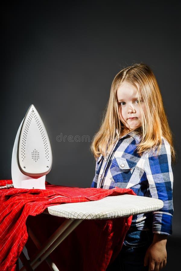 Nettes kleines Mädchen, das Ihrer Mutter durch das Bügeln von Kleidung, Contras hilft stockfotos
