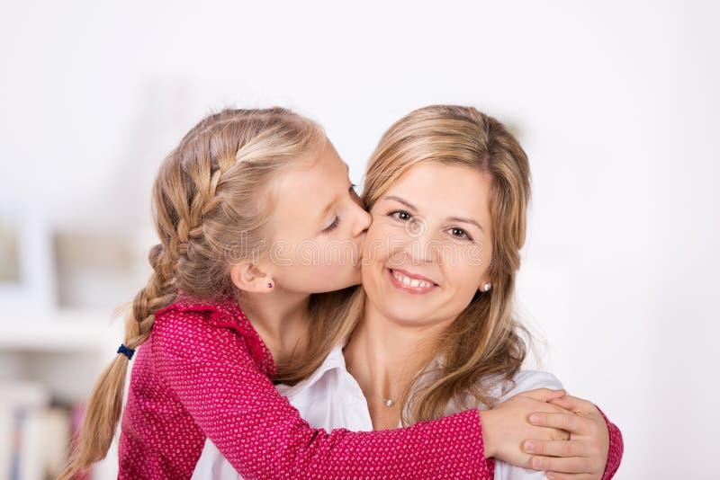 Nettes kleines Mädchen, das ihrer Mutter einen Kuss gibt stockfotos