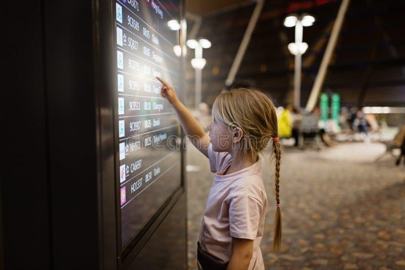Nettes kleines M?dchen, das Ikone auf digitalem Touch Screen im Flughafenabfertigungsgeb?ude bedr?ngt Kind unter Verwendung der T stockfotos