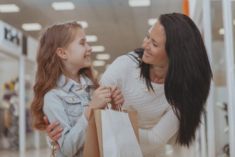 Nettes kleines Mädchen, das im Einkaufszentrum mit ihrer Mutter kauft stockfotografie