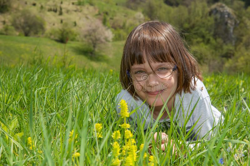 Nettes kleines M?dchen, das im Gras und im Lachen liegt stockbilder