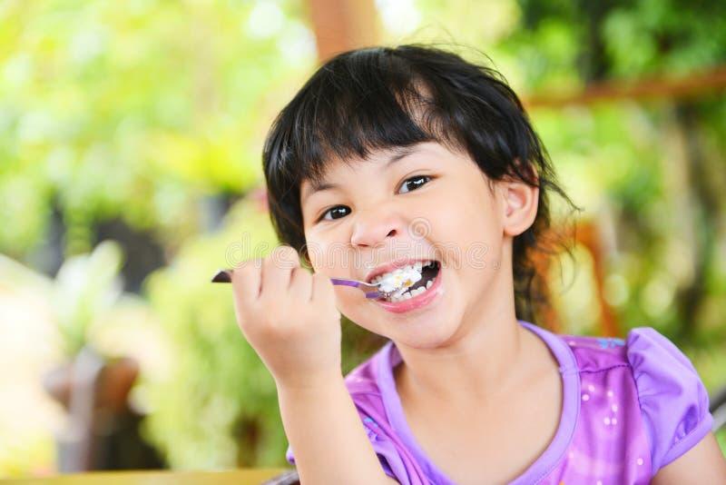 Nettes kleines Mädchen, das Kuchen - asiatisches Kind glücklich isst und einen Löffel in den Mund mit Kuchen auf Speisetische, se stockfotos