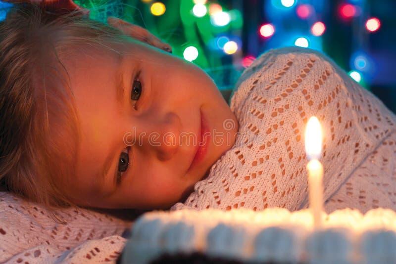 Nettes kleines Mädchen, das Kuchen betrachtet stockfotografie