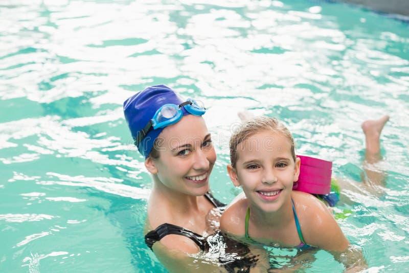 Nettes kleines Mädchen, das lernt, mit Trainer zu schwimmen stockbilder
