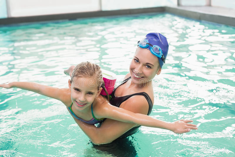 Nettes kleines Mädchen, das lernt, mit Trainer zu schwimmen stockbild
