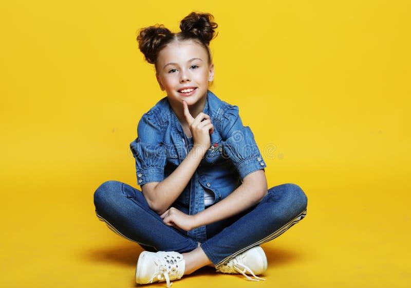 Nettes kleines Mädchen, das, lokalisiert auf gelbem Hintergrund sitzt und lächelt lizenzfreie stockfotografie
