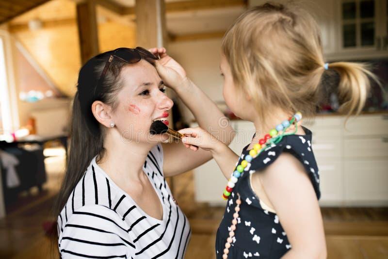 Nettes kleines Mädchen, das Make-up ihre attraktive Mutter mit Bürste antut stockfotografie