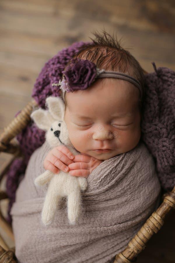 Nettes kleines Mädchen, das mit einem Spielzeug im Korb, Farbe schläft stockfotografie