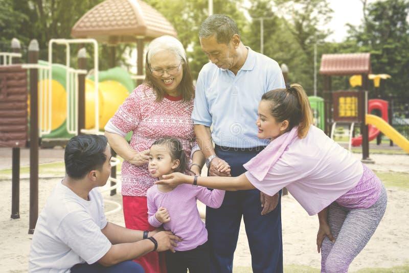 Nettes kleines Mädchen, das mit ihrer Familie im Park spielt stockfotografie
