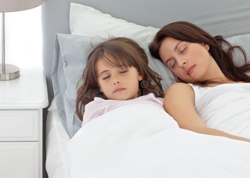 Nettes kleines Mädchen, das mit ihrer Mutter schläft stockfoto