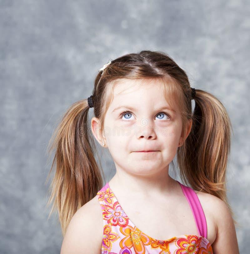 Nettes kleines Mädchen, das oben in Richtung des copyspace blickt lizenzfreie stockfotos