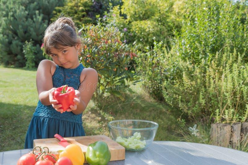 Nettes kleines Mädchen, das roten Pfeffer für Sie zeigt lizenzfreie stockfotos