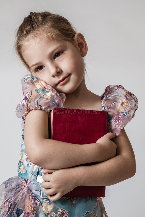 Nettes kleines Mädchen, das rotes Buch umarmt stockbild