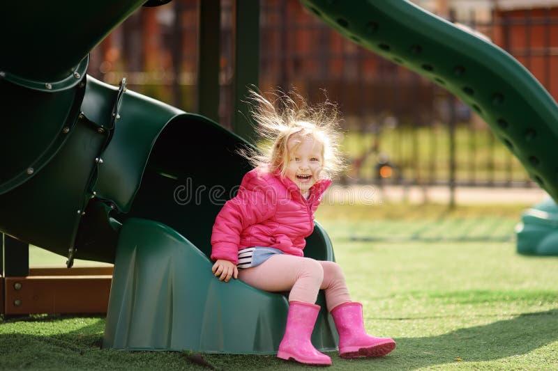 Nettes kleines Mädchen, das Spaß auf Spielplatz im Freien hat Kind auf Plastikdia stockbilder